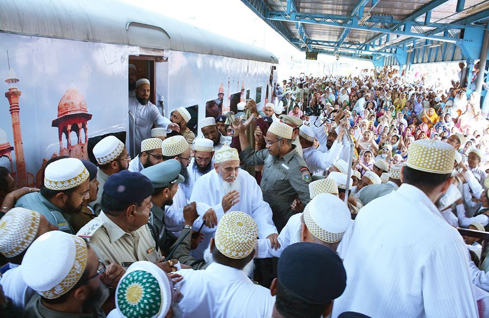 Syedna greets community members during a brief stop at a train station in Indore.